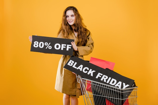Smiling woman has black friday 80% off sign with cart full of shopping bags and signal tape isolated over yellow
