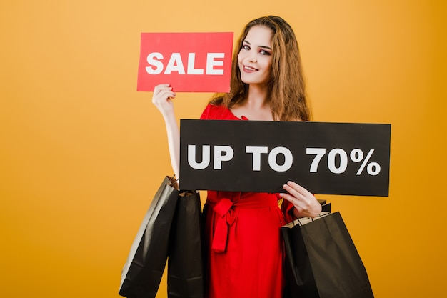 Smiling woman has sale up to 70% sign with paper shopping bags isolated over yellow