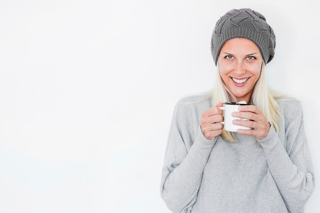Smiling woman in hat holding hot drink