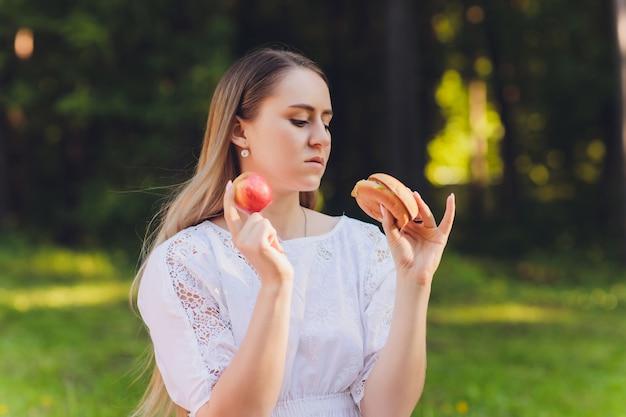 Улыбающаяся женщина расслабляющий перерыв на обед на открытом воздухе, она сидит на траве и ест.