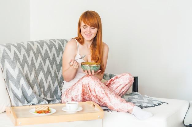 Smiling woman having breakfast on sofa