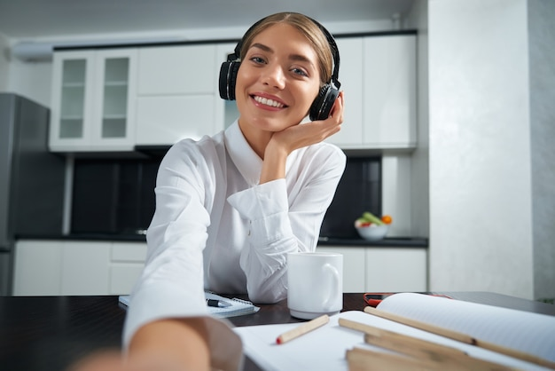 Smiling woman in headphones having video call on laptop