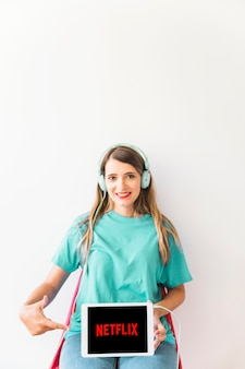 Smiling woman in headphones pointing at netflix logo