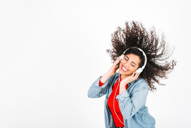 Smiling woman in headphones shaking hair