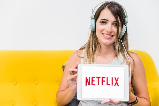 Smiling woman in headphones showing netflix logo