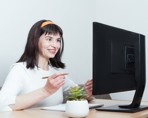 Smiling woman in headphones sitting at the table at home looking at the monitor screen, talking on video communication, taking notes
