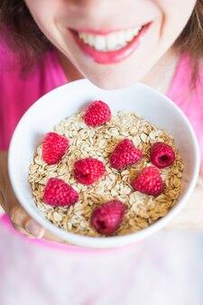 Улыбающаяся женщина держит в миске здоровый и естественный завтрак, овсянку и малину.