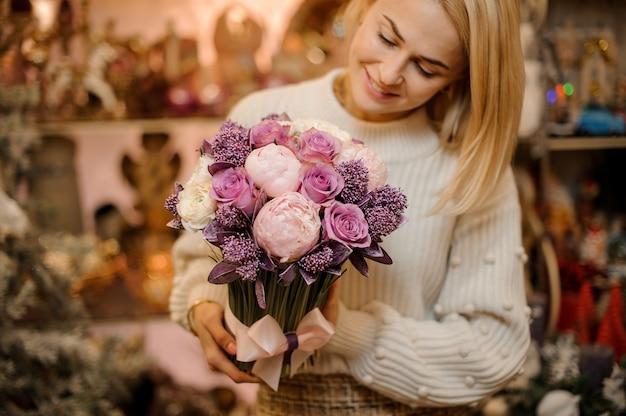 녹색 줄기와 부드러운 분홍색과 보라색 꽃의 꽃다발을 들고 웃는 여자
