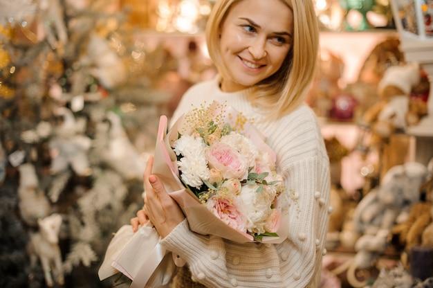 작은 가지와 녹색 잎으로 장식 된 부드러운 분홍색 모란 장미 꽃다발을 들고 웃는 여자