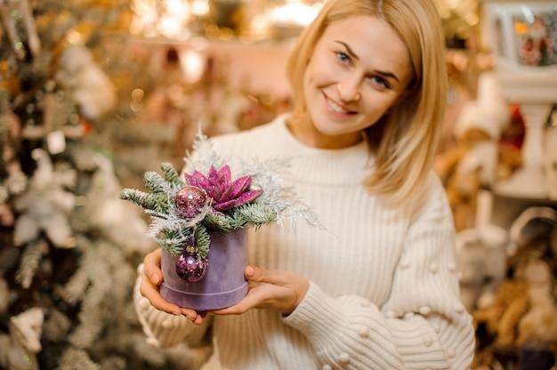 장식품으로 장식 된 핑크색 반짝이로 덮여 녹색 즙이 많은 상자를 들고 웃는 여자