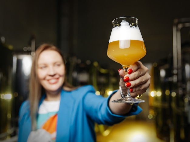 ビールのガラスを保持している笑顔の女性