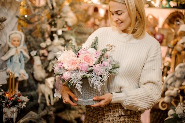전나무 나뭇 가지로 장식 된 밝은 분홍색 모란 장미와 회색 스웨터 패턴 상자를 들고 웃는 여자