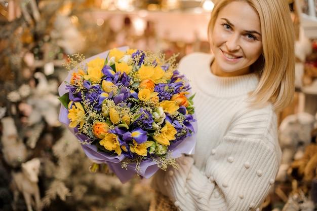 선물 종이에 싸서 보라색과 흰색 꽃과 작은 꽃다발을 들고 웃는 여자