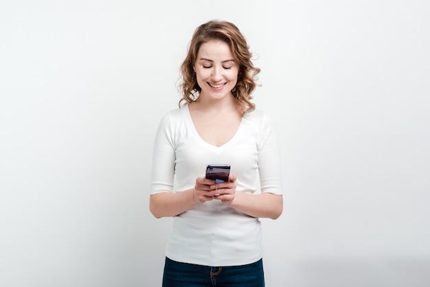 Улыбающиеся женщина держит телефон в руке.