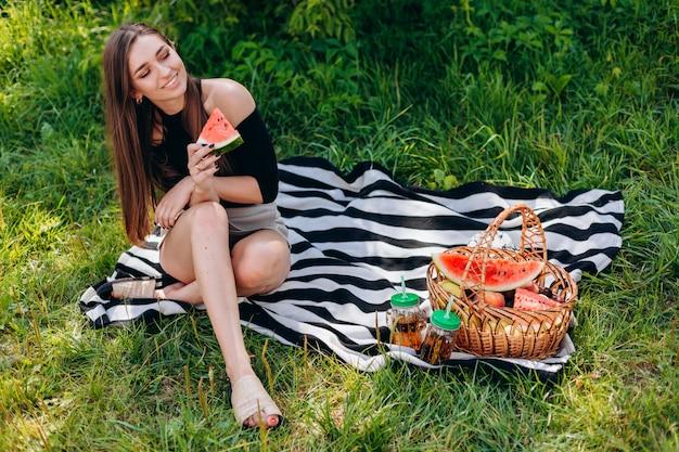 야외 공원에서 피크닉을 데 수박 한 조각을 들고 웃는 여자
