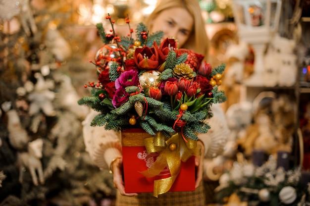 モミの木の枝で飾られたさまざまな明るい花と金のテープで赤い箱を保持している笑顔の女性