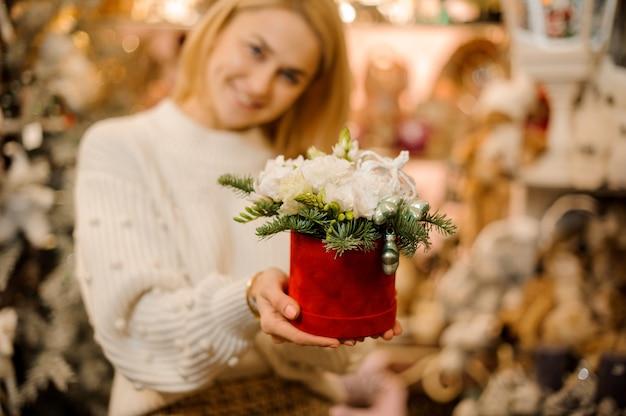 전나무 나뭇 가지로 장식 된 흰색 꽃과 빨간색 상자를 들고 웃는 여자