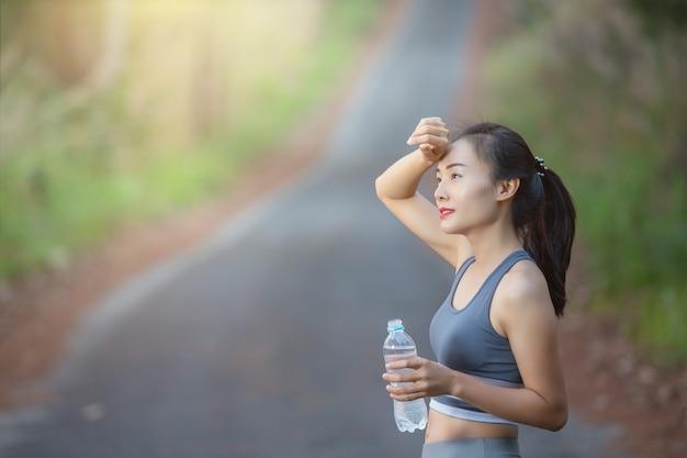 水のボトルを保持している女性の笑みを浮かべてください。