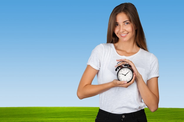 Smiling woman holding alarm watch