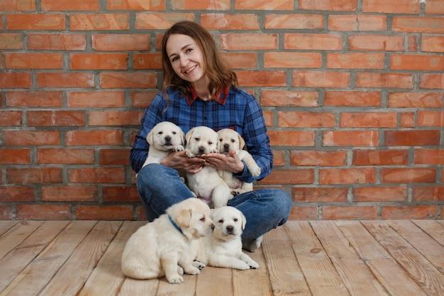テキストのコピースペースとレンガの背景に多くのラブラドール子犬を保持し、世話をする笑顔の女性 Premium写真
