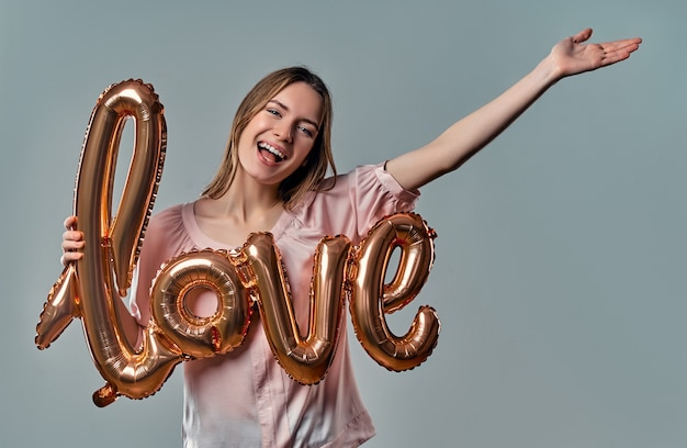 Smiling woman holding balloon labeled love and looking at camera over gray.