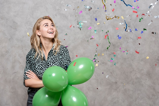 Smiling woman holding balloons surrounded by confetti