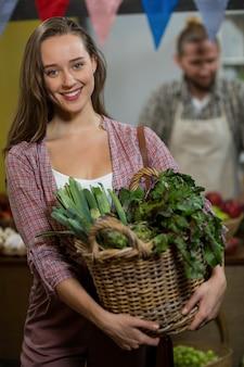 식료품 점에서 녹색 잎이 많은 채소 바구니를 들고 웃는 여자
