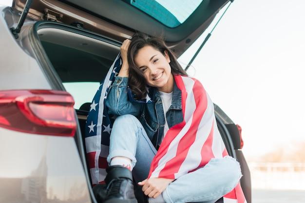 Улыбающиеся женщина держит большой флаг сша в багажнике