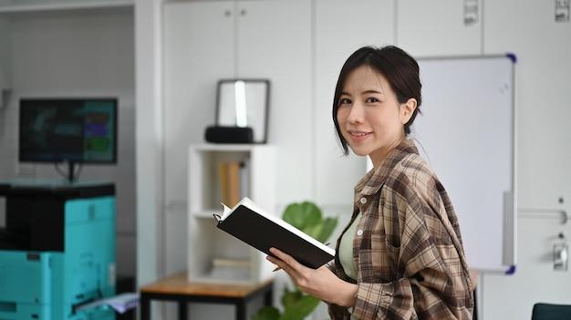 Улыбается женщина, держащая книгу и глядя на камеру, стоя в офисе.