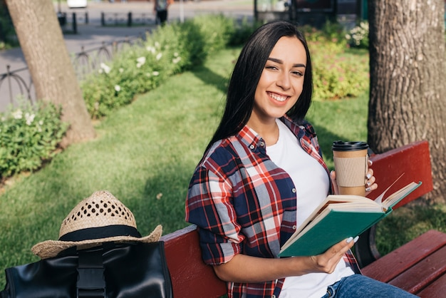 Smiling woman holding book and disposable coffee cup while sitting on bench at park