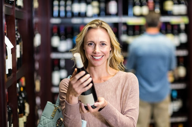 Smiling woman holding bottle of wine