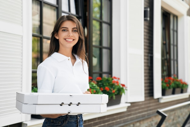Smiling woman holding boxes of pizza