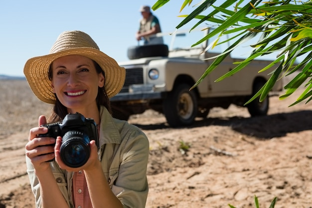 Smiling woman holding camera with man on off road vehicle