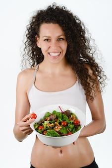 Donna sorridente che tiene un pomodoro ciliegia e un insalata