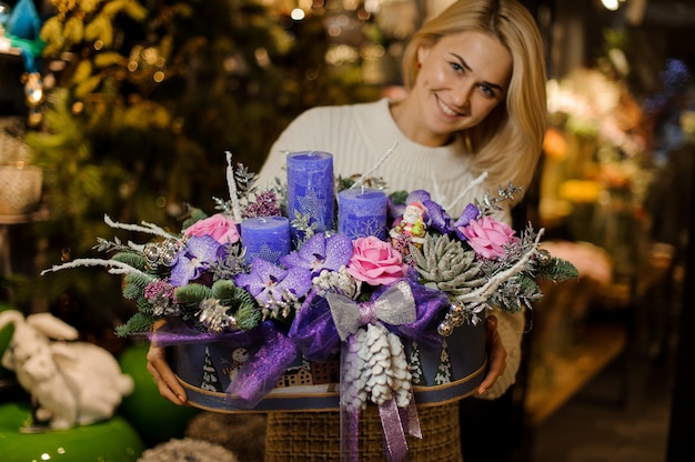 Smiling woman holding a christmas composition with purple and pink flowers, succulents, fir-tree and candles