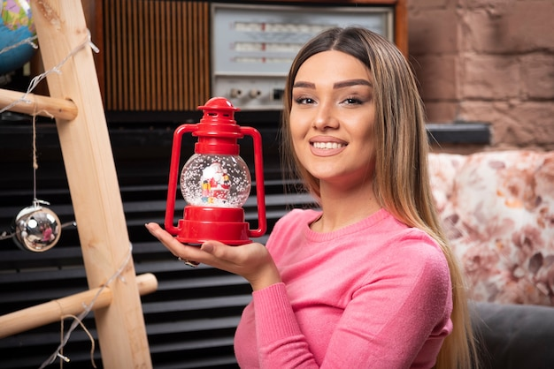 A smiling woman holding a christmas red lamp . high quality photo