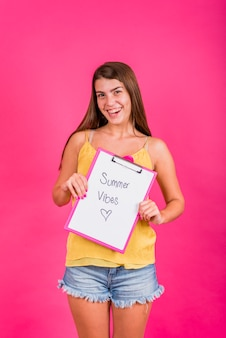 Smiling woman holding clipboard with text summer vibes