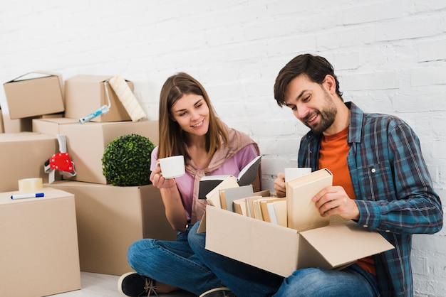 Smiling woman holding coffee cup in hand looking at her husband looking at book in the box