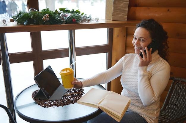 コーヒーの紙コップを持って、カフェテリアに座って携帯電話で話している笑顔の女性。カフェでのビジネス。