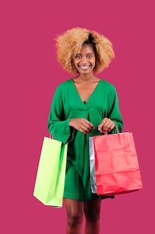 Улыбающаяся женщина, держащая красочные хозяйственные сумки, стоя на изолированном фоне. концепция продажи черная пятница.