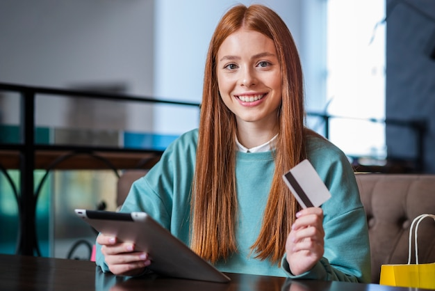 Smiling woman holding credit card and tablet