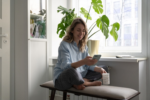 Smiling woman holding cup of coffee at home, using mobile smart phone, chatting in social networks