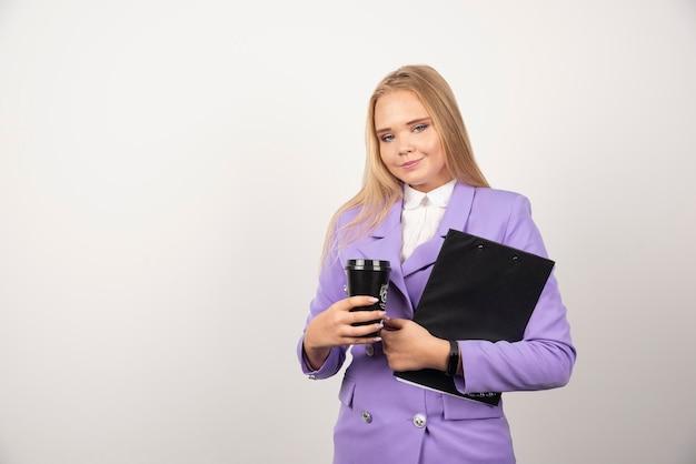 Donna sorridente che tiene tazza di caffè e tablet su sfondo bianco. foto di alta qualità