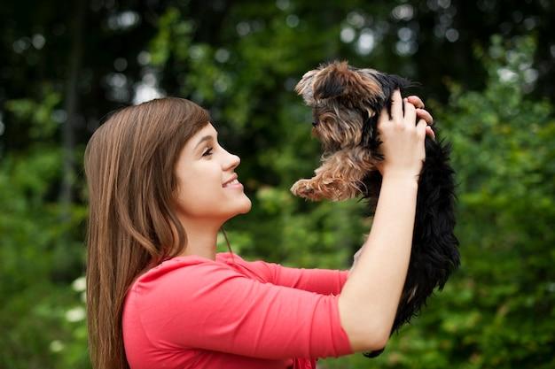 Donna sorridente che tiene cucciolo carino