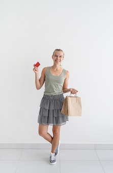 環境にやさしい買い物袋とクレジットカードを持っている笑顔の女性