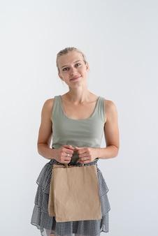 環境にやさしい買い物袋を持っている笑顔の女性
