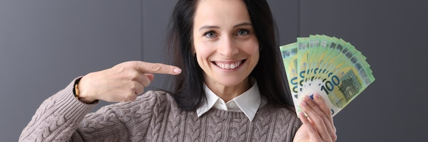 Smiling woman holding fan of money. fast money online concept