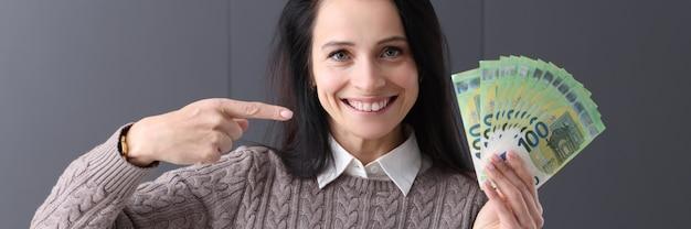 Улыбается женщина, держащая вентилятор денег. онлайн-концепция быстрых денег
