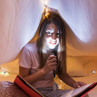 Smiling woman holding flashlight over face under bed sheet reading book