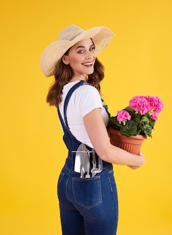 Smiling woman holding flower pot with beautiful flowers